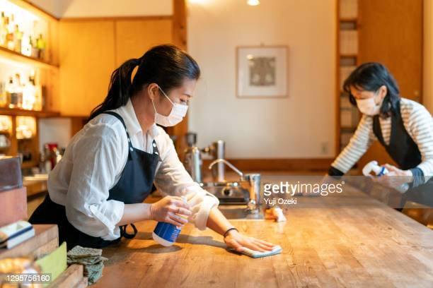 two women wearing a mask, carefully wipe a counter  and enthusiastically disinfect in preparation for opening - tokyo japan stock pictures, royalty-free photos & images