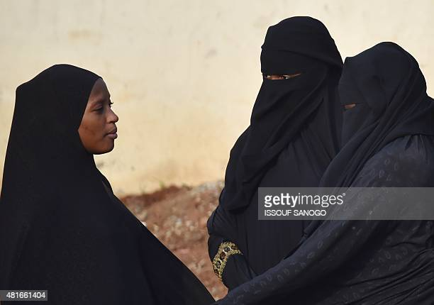Two women wearing a niqab speak with a person wearing a tchador on July 23 2015 in a street of Abidjan where the full veil is not forbidden AFP PHOTO...