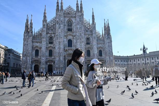Two women wearing a protective facemask walk across the Piazza del Duomo, in front of the Duomo, in central Milan, on February 24, 2020 closed...