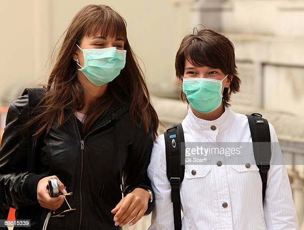 Two women wearing a surgical masks to prevent the transmission of airborne infection walk in Westminster on July 30 2009 in London England Figures...