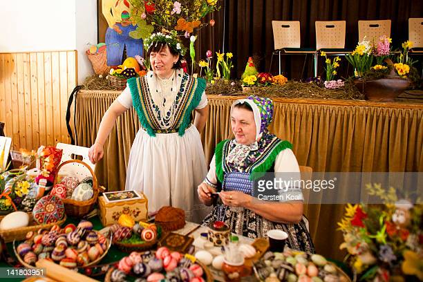 Two women wearing a traditional Lusatian sorbian folk dress talk at the annual Sorbian Easter egg market on March 24 2012 in Schleife near...