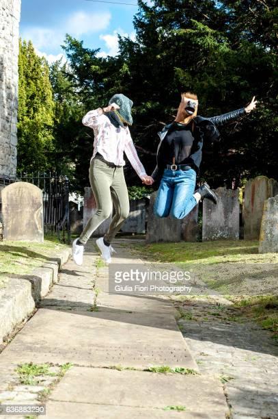 Two women wearing animal rubber masks