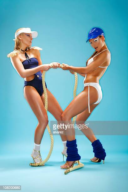 Two Women Wearing Bathing Suits and Tugging on Rope