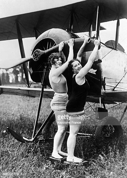 Two women wearing bathing suits are playing with a plane propeller in a field on July 22 1929