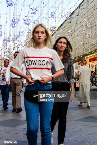 two women wearing casual clothes and a t-shirt with the words slow down walks towards the camera in a pedestrian street in moscow, russia - sergio amiti stock pictures, royalty-free photos & images