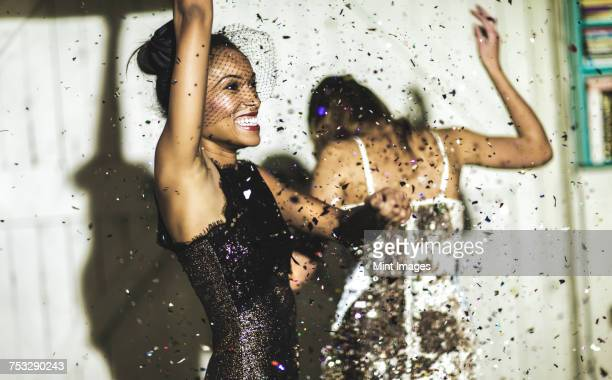 two women wearing cocktail dresses at a party dancing in a shower of glitter confetti. - cocktail dress stock pictures, royalty-free photos & images