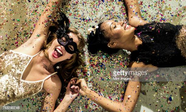 Two women wearing cocktail dresses at a party lying on the floor in a shower of confetti.