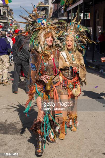 two women wearing costumes walking in the street during the mardi gras celebration at new orleans carnival, louisiana, usa. - creole ethnicity stock pictures, royalty-free photos & images