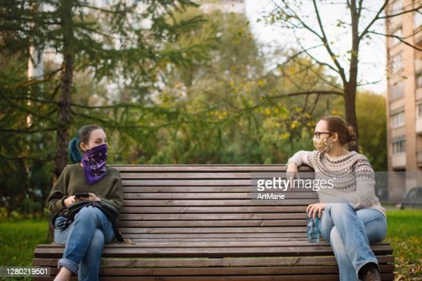 使い捨ての保護マスクまたはバンダナの顔を覆い、社会的な離散性を持つベンチに座っている2人の女性 - ゲートル ストックフォトと画像