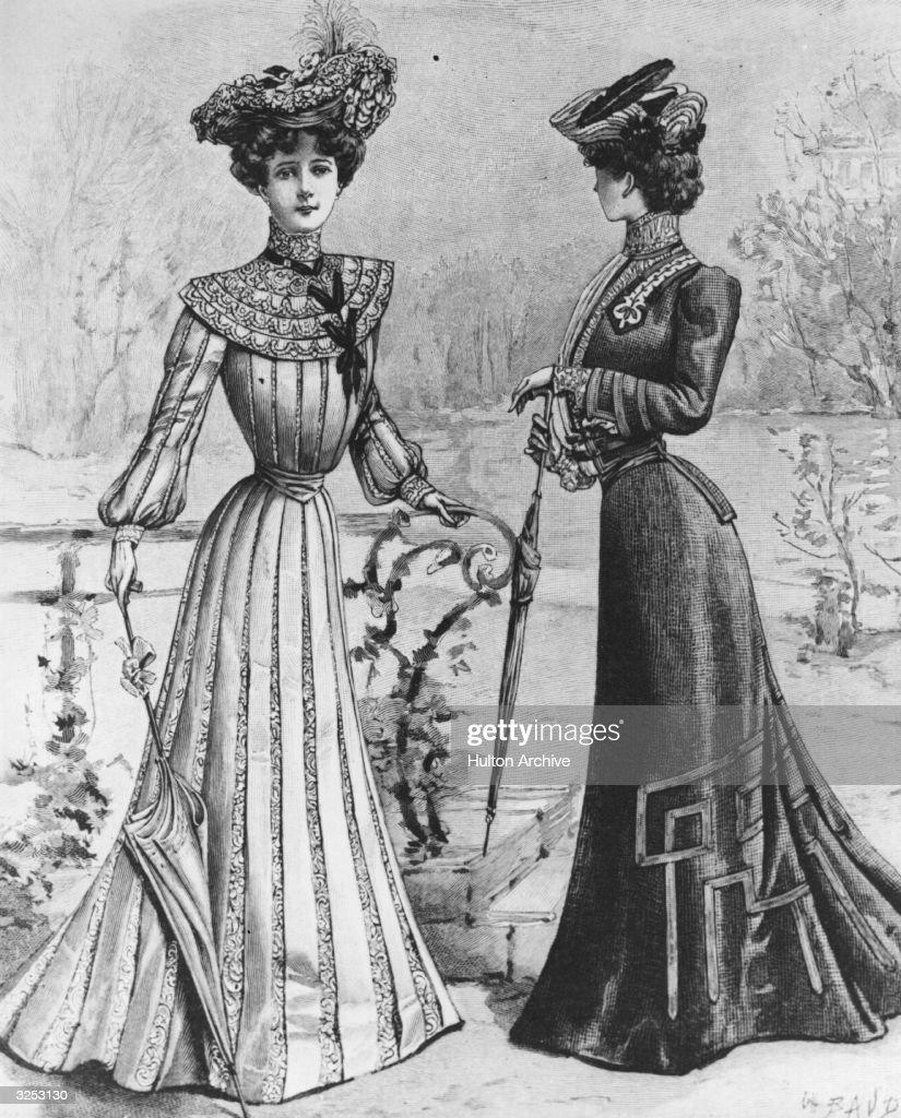 Two women wearing elegant Edwardian street dresses in a park.