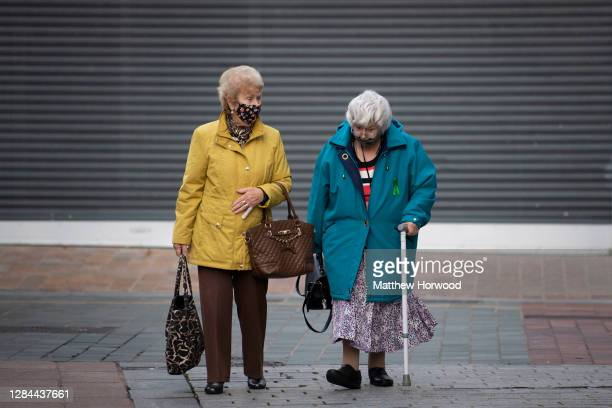 Two women wearing face coverings walk through the town centre on November 7, 2020 in Merthyr Tydfil, Wales. Merthyr Tydfil, with 741 cases per...