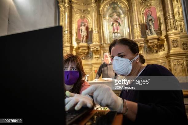 Two women wearing face masks as a preventive measure against covid19 setting up the computer during the mass of resurrection Easter in Spain is...