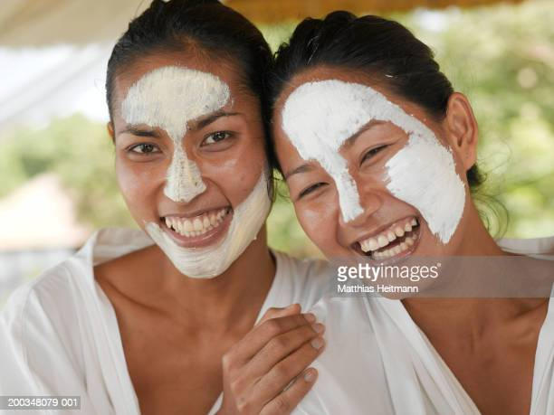 Two women wearing face masks, laughing, close-up, portrait