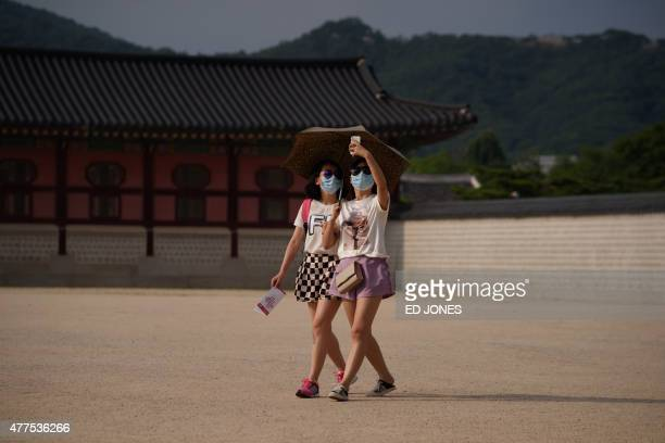 Two women wearing face masks take a 'selfie' as they walk in the grounds of Gyeongbokgung palace in Seoul on June 18 2015 South Korea's evergrowing...