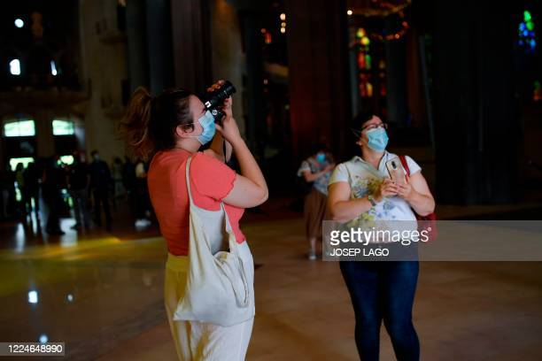 Two women wearing face masks visit the Sagrada Familia basilica in Barcelona on July 4, 2020 as it reopens with a tribute to healthcare workers...