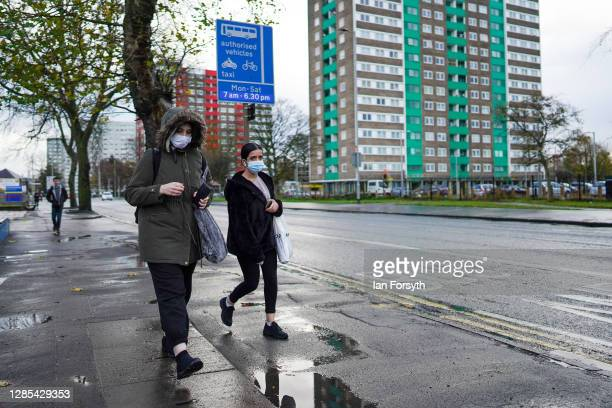 Two women wearing face masks walk down the street outside Hull Royal Infirmary on November 13, 2020 in Hull, England. Hull recorded 726.8 new cases...