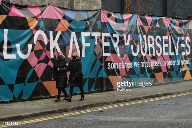 Two women wearing face masks walk next to a coronavirus related billboard in Dublin city centre during Level 5 Covid-19 lockdown. In Dublin during...