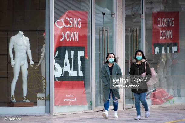 Two women wearing face masks walk past a store with a closing down sign in Cardiff city centre on March 13, 2021 in Cardiff, Wales. Wales First...