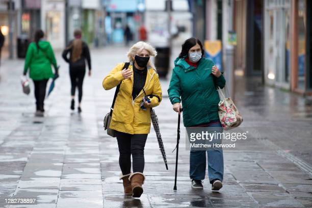 Two women wearing face masks walk through the town centre on October 28, 2020 in Bridgend, Wales. Wales entered a national lockdown on Friday evening...