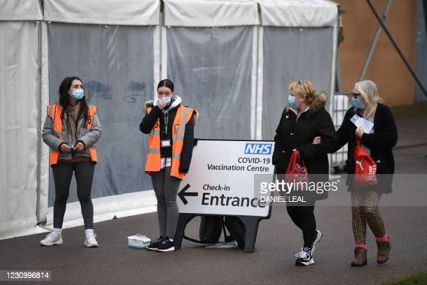 Two women wearing facemasks walk past volunteers at a temporary vaccination hub set up to administer a Covid-19 vaccine, at the Colchester Community...