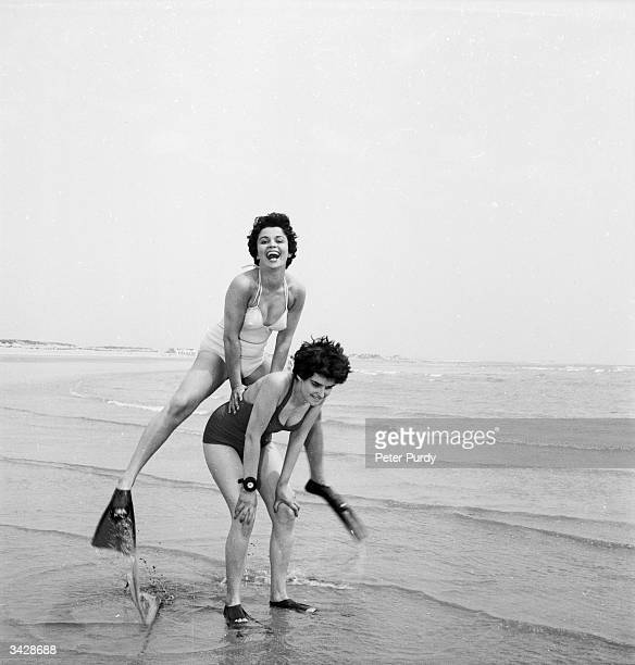 Two women wearing fins play leapfrog on the beach