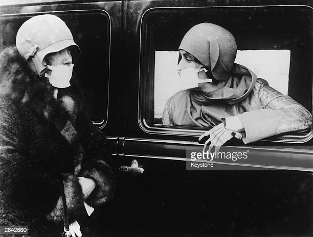 Two women wearing flu masks during a flu epidemic in 1929.