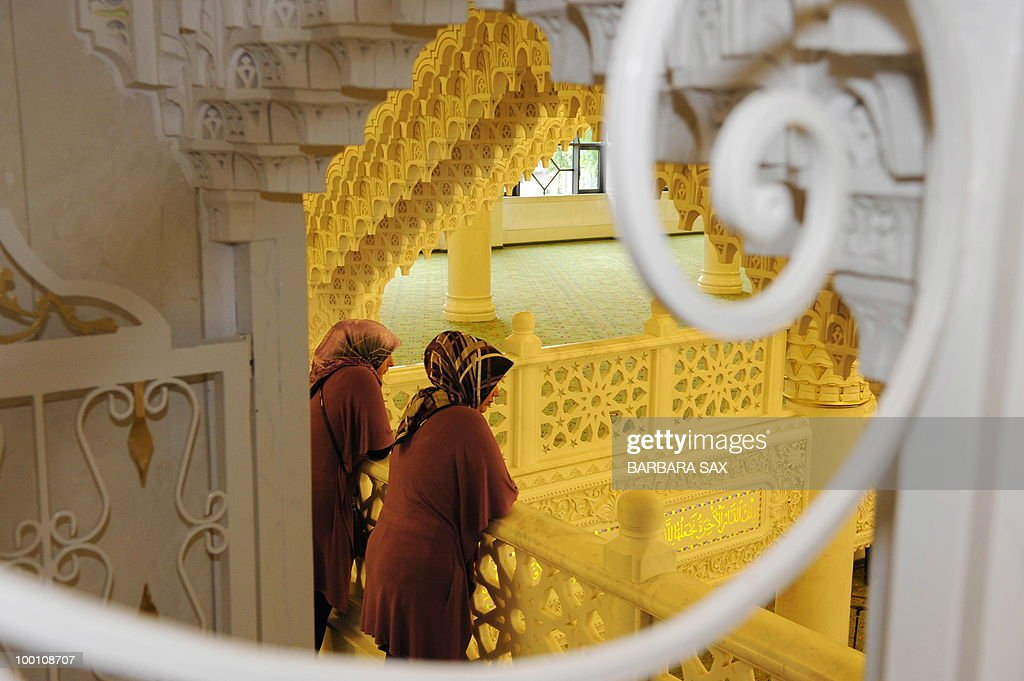 Two women wearing headscarves watch from a gallery of the new Omar Mosque in Berlin's Kreuzberg district during the inauguration of the Islamic Maschari Centre on May 21, 2010. The centre includes the mosque, a kindergarden, a school, a library, a travel agency and a shopping centre.