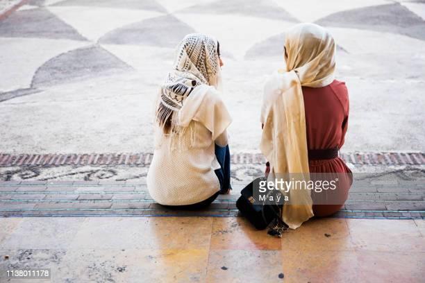 due donne che indossano hijab sittinh sulle scale - velo foto e immagini stock