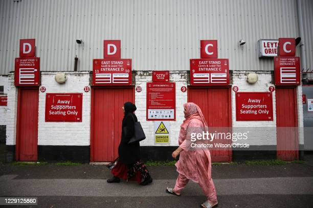 Two women wearing hijabs walk past the closed turnstiles at The Breyer Group Stadium ahead of the Sky Bet League Two match between Leyton Orient and...
