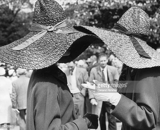 Two women wearing large, floppy brimmed, straw hats have a chat during a visit to the Chelsea Flower Show. The one on the left is navy the one on the...