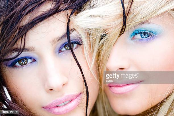 Two Women Wearing Make-Up and Smiling Close Together