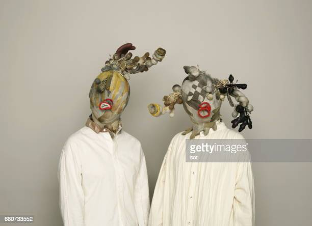 Two women wearing mask made of work gloves