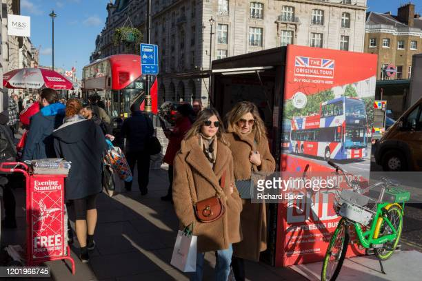 Two women wearing matching coats walk in winter sunshine opposite the Ritz Hotel on Piccadilly in central London on 11th February 2020 in London...