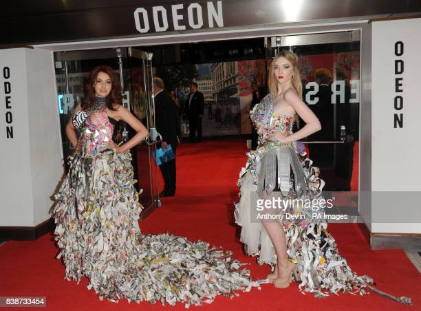 Two women wearing paper dresses pose at the Royal Film Performance 2011 of Hugo at the Odeon Cinema in Leicester Square London