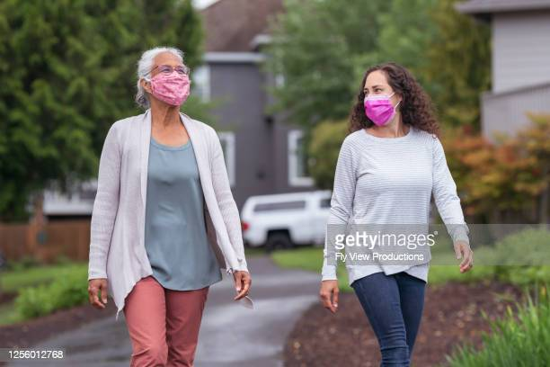two women wearing protective face masks enjoying the outdoors during coronavirus - coronavirus mask stock pictures, royalty-free photos & images
