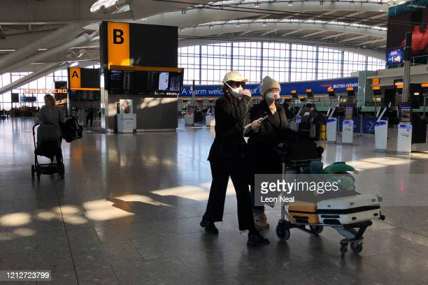 Two women wearing protective masks walk through departures at terminal 5 of Heathrow Airport on March 16 2020 in London England As the coronavirus...
