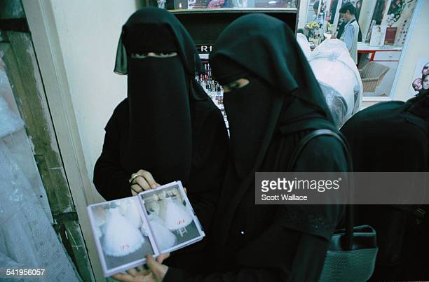 Two women wearing the abaya and niqab visit a wedding dress shop in Aden Yemen 2004