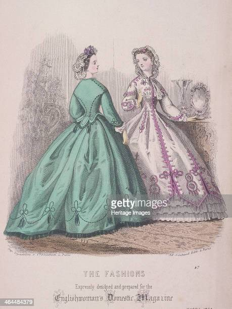 Two women wearing the latest fashions 1864 Both of the women are wearing dresses with tight fitting bodices and full hooped skirts One can see the...