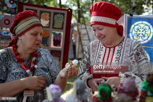 Two women wearing traditional costumes talk at a park during a folk fest for the celebrations of the 294th anniversary of the city of Ekaterinburg...