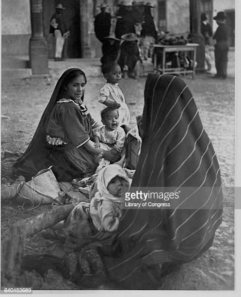 Two women wearing traditional dress play with their young children at the plaza in Patzcuaro. Michoacan, Mexico.
