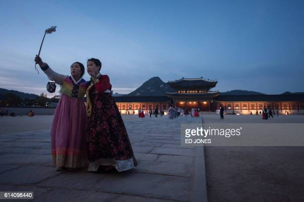 TOPSHOT Two women wearing traditional hanbok dresses pose for a selfie before Gyeongbokgung palace in Seoul on October 12 2016 Samsung Electronics...