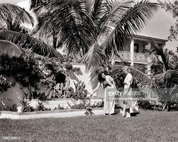 Two Women Wearing Trousers Walking In Yard Admiring The Tropical Garden Of Home Sunset Islands Miami Beach Florida