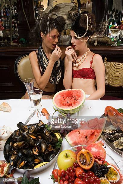 Two women wearing underwear enjoying a banquet