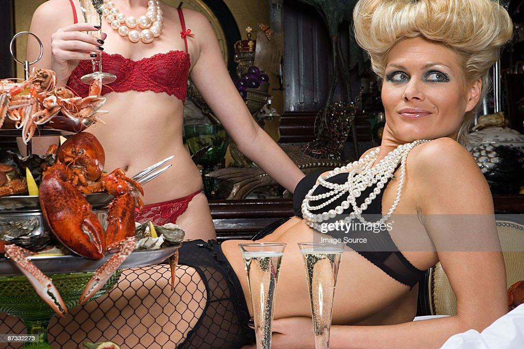 Two women wearing underwear in a banquet hall : Stock Photo