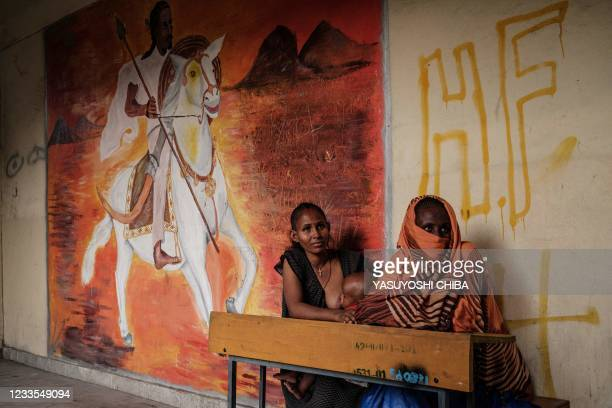 Two women, who fled the violence in Ethiopia's Tigray region, sit next to a painting at May Weyni secondary school, now hosting 10,500 displaced...