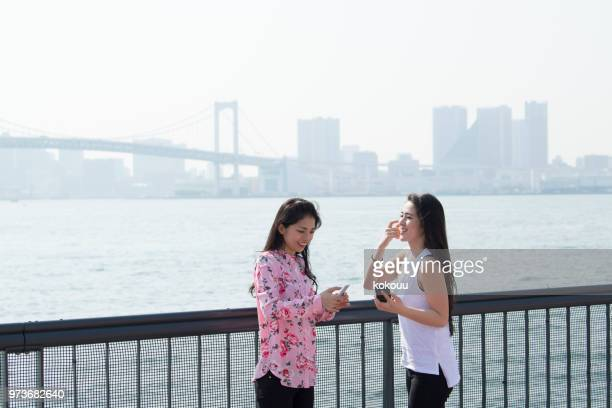 two women who have conversation while watching the ocean with a cell phone. - asian twins stock photos and pictures