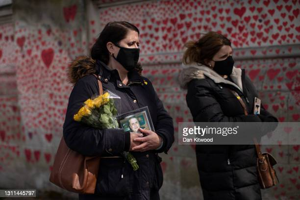 Two women who have lost family members walk along a memorial wall next to the river thames in Westminster on April 08, 2021 in London, England. The...
