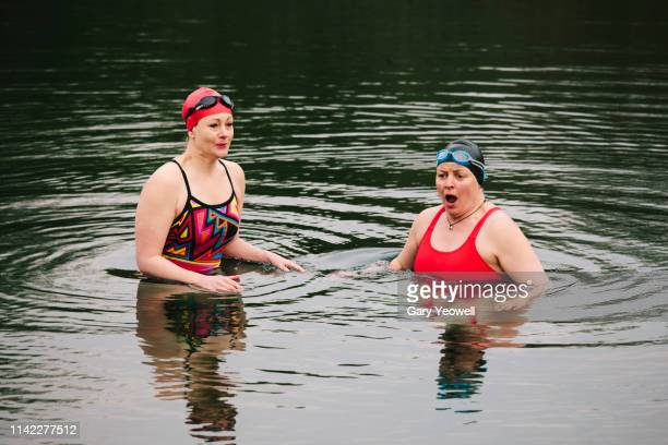 two women wild swimmers in a lake - cold temperature stock pictures, royalty-free photos & images