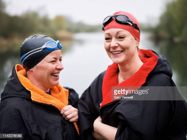 two women wild swimmers laughing by a lake - winning stock pictures, royalty-free photos & images