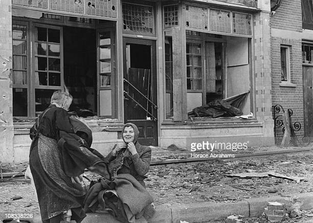 Two women with a pet kitten outside the ruins of their shop in the village of Wagenberg Netherlands November 1944